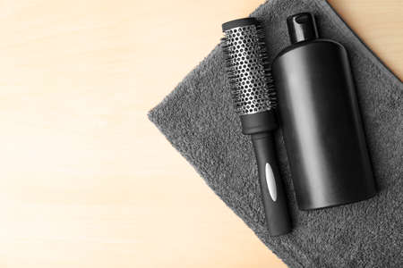 Bottle with shampoo and comb on wooden background Stock Photo