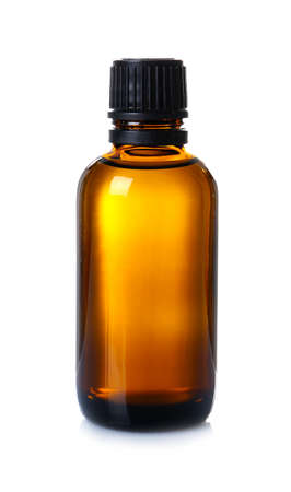 Glass bottle with essential cinnamon oil on white background Stock Photo