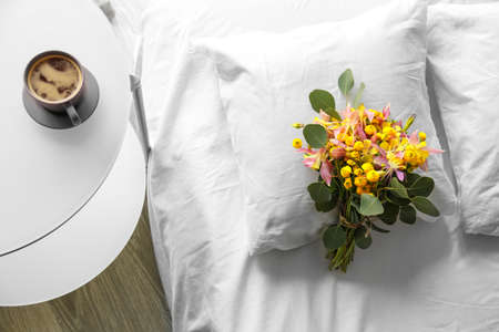 Beautiful flower bouquet on bed Stock Photo