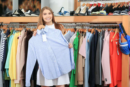 Young woman choosing shirt in mall