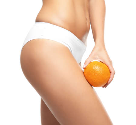 Young woman holding orange on white background. Cellulite problem concept Standard-Bild