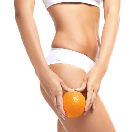 Young woman holding orange on white background. Cellulite problem concept Stock Photo