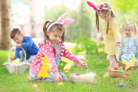 Children having fun in park. Easter egg hunt concept Stock Photo - 98384274