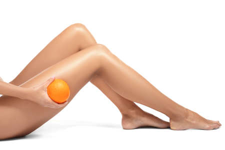 Female legs and orange on white background. Cellulite problem concept