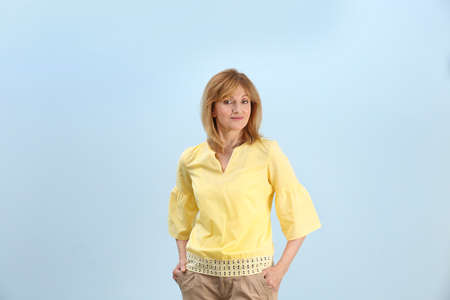 Portrait of attractive mature woman on light blue background
