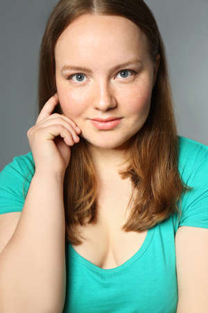 Overweight young woman on gray background. Diet concept Stock Photo