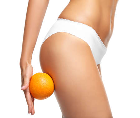 Young woman holding orange on white background. Cellulite problem concept