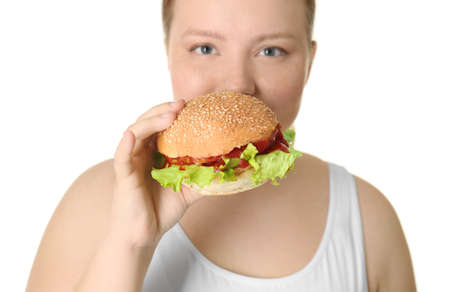 Overweight young woman with burger on white background. Diet concept Stock Photo