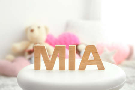 Baby name MIA composed of wooden letters on stool. Choosing name concept