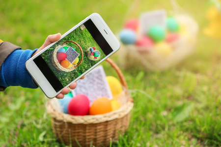 Little boy scanning QR Code in basket with colorful eggs at park. Easter hunt concept Stock Photo