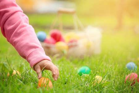 Little girl gathering colorful egg in park. Easter hunt concept Reklamní fotografie