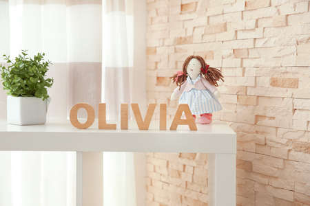 Baby name OLIVIA composed of wooden letters on shelf. Choosing name concept