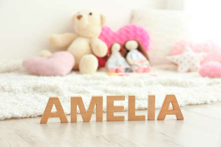 Baby name AMELIA composed of wooden letters on floor. Choosing name concept Stock Photo