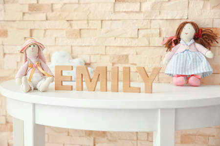 Baby name EMILY composed of wooden letters on table. Choosing name concept