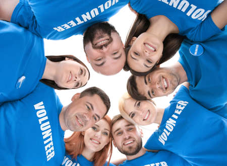 Young volunteers with their heads together in circle on white background