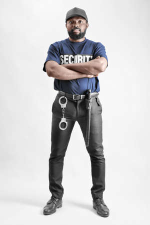 Male security guard standing on light background Stock Photo