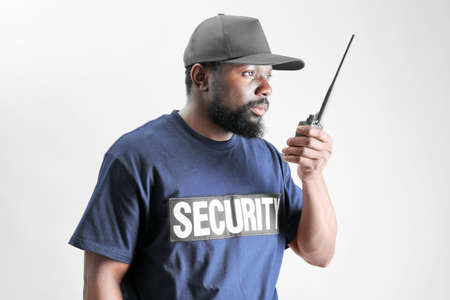 Male security guard using portable radio on light background