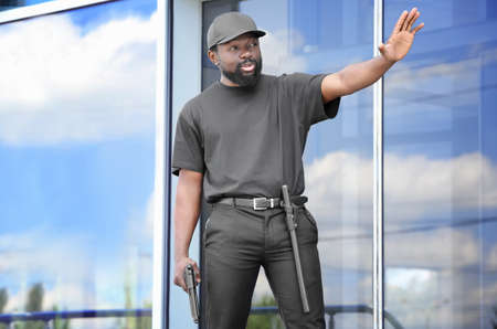 Male security guard showing stop gesture near big modern building