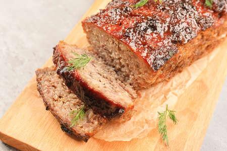 Tasty baked turkey meatloaf on wooden board