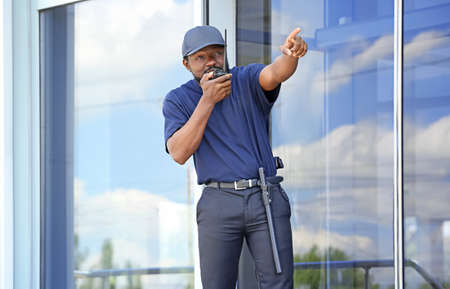 Male security guard using portable radio transmitter near big modern building Stock Photo