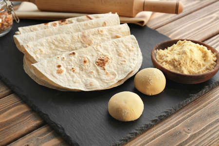 Slate plate with delicious tortillas on wooden table