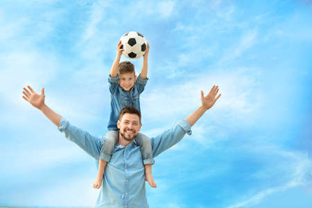 Dad and son with soccer ball outdoors Imagens