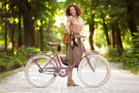 Beautiful young woman with bicycle, outdoors