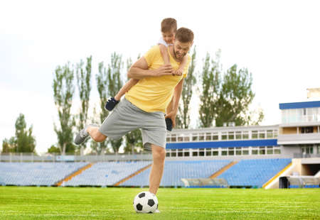 Dad and son playing football together in stadium Foto de archivo