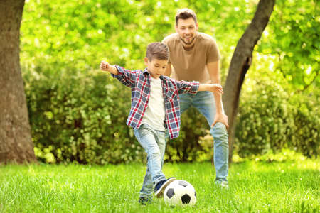Dad and son playing football together on green meadow Foto de archivo