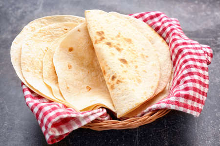 Wicker basket with delicious tortillas on table
