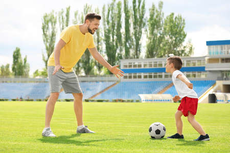 Dad and son playing football together in stadium Archivio Fotografico
