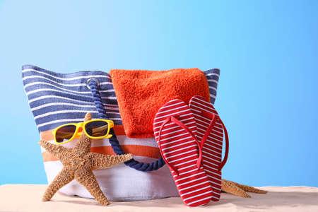 Composizione con accessori da spiaggia sulla sabbia su sfondo di colore. Concetto di vacanze estive% 00