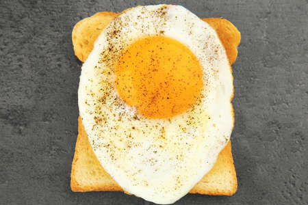 Delicious sunny side up egg with bread on table