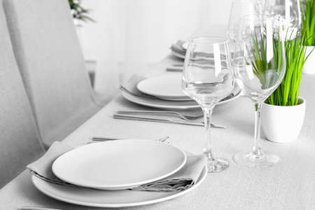 Beautiful table setting with green plant and grey napkins