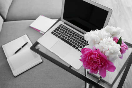 Bouquet of beautiful peonies and laptop on glass table in room