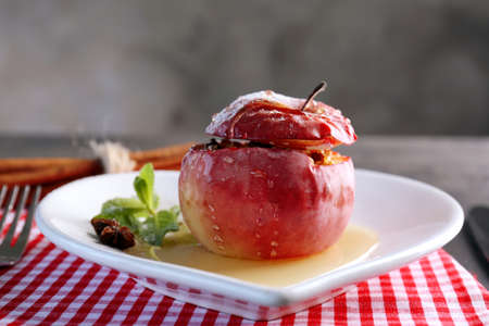 Plate with tasty baked apple on table, closeup Stock Photo