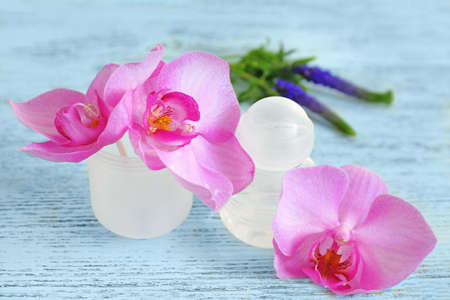 Female deodorant and flowers on wooden table