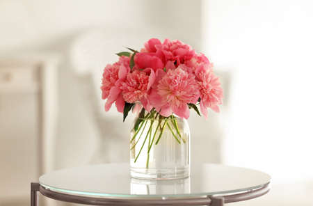 Glass vase with beautiful peonies on table Stock fotó