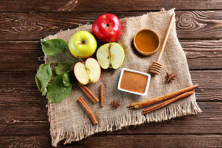 Composition with fresh apples and cinnamon on wooden table Stock Photo
