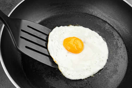 Homemade over easy egg with spatula in frying pan