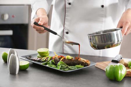 Chef vertiendo pescado con deliciosa salsa en el restaurante