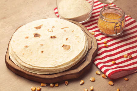 Wooden board with delicious tortillas on kitchen table