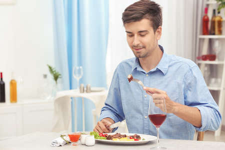 Young man eating delicious ribs in restaurant