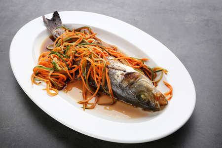 Plate with delicious fish, sauce and vegetables on table