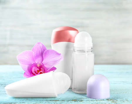 Different deodorants and orchid flower on wooden background