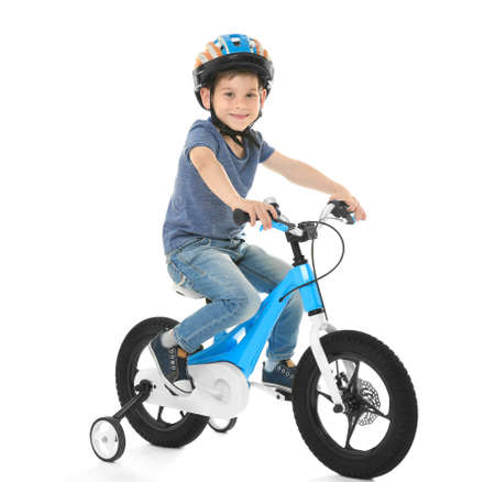 Cute little boy riding bicycle on white background