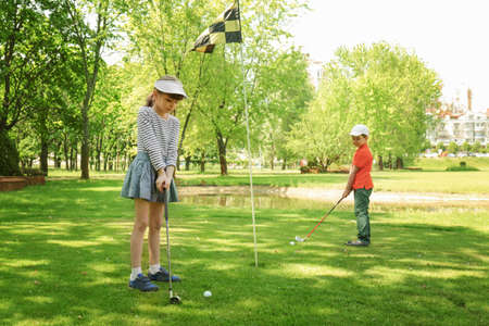 Cute children playing golf on course in sunny day