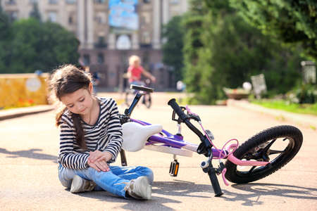 Cute little girl fallen off her bicycle outdoors