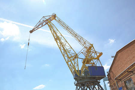 Hoisting crane against blue sky