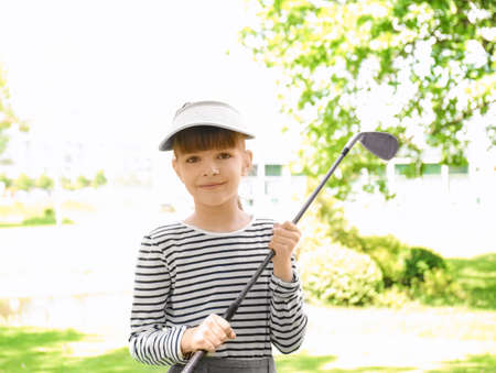 Cute girl on golf course in sunny day